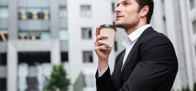 thoughtful-young-businessman-drinking-take-away-coffee-and-thinking-near-business-center